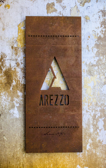 Metal signage with antiqued rust finish